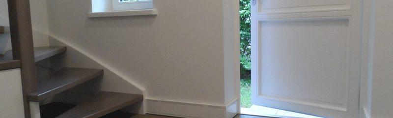 Elpan met eindstukken tegen de trap en naast het deur kozijn.